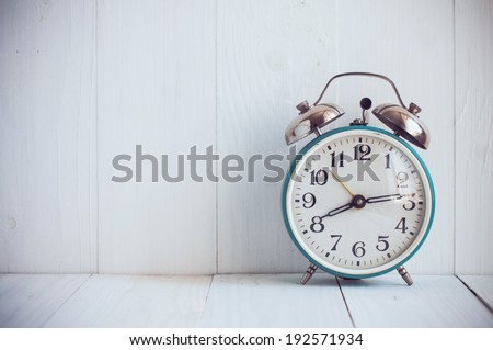 Big old vintage alarm clock with bells, painted white wooden background