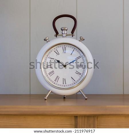 Big old vintage clock on wooden table