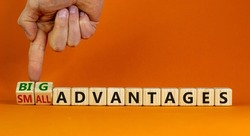 Big or small advantages symbol. Businessman turns wooden cubes, changes words Small advantages to big advantages. Beautiful orange background, copy space. Business, small or big advantages concept.