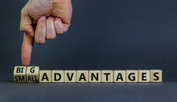 Big or small advantages symbol. Businessman turns wooden cubes, changes words Small advantages to big advantages. Beautiful grey background, copy space. Business, small or big advantages concept.