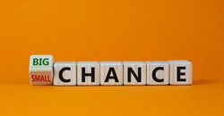 Big or small chance. Turned cubes and changed the words 'small chance' to 'big chance' or vice versa. Beautiful orange background. Business concept. Copy space.