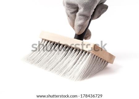 Big paintbrush in hand isolated on white background.