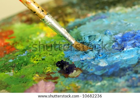 big paintbrush is mixing colors on palette. Shallow DOF