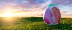 big painted colorful watercolor easter egg at easter on sunrise or sunset on a meadow landscape, Panoramic backgroud, with copyspace for your individual text.