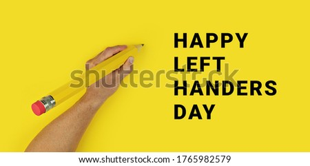 Photo of  Big pencil in male left hand on yellow background with text Happy Left Handers Day. Conceptual banner for celebration of international left-handed day