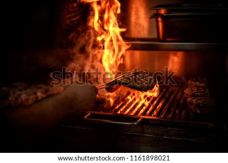 Big piece of meat being grilled on hot steamy glowing fire. Large meat burger. BBQ restaurant.