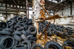 Big pile of automobile tires on the broken-down plant. Many black rubber tyre on the ground inside the old huge empty building