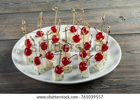 Big plate full of dor blu cheese cubes served with cherries appetizers food eating delicious menu restaurant cafe gourmet traditional hunger appetite dish serving concept. #761039557