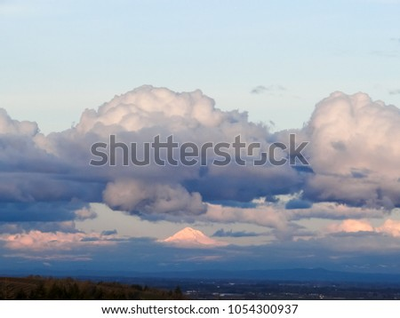 Big, plump clouds hang over the snow covered peak of Oregon's Mt. Hood, glowing in reflected afternoon sun, blue haze under the peak. #1054300937