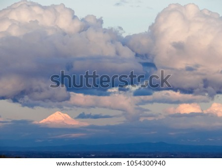 Big, plump clouds hang over the snow covered peak of Oregon's Mt. Hood, glowing in reflected afternoon sun, blue haze under the peak. #1054300940