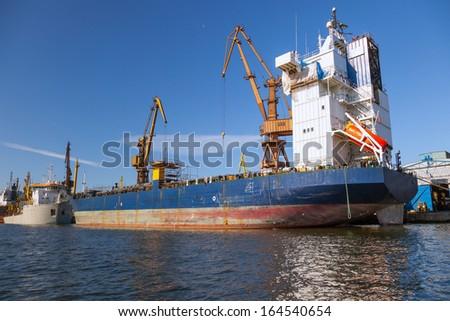 Big port cranes and a cargo ship. - stock photo