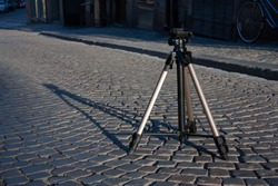 Big professional photography tripod placed on a cobblestone street, illuminated by sun giving a long shadow.