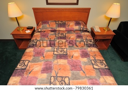 Big queen sized clean bed with lighted lamps at bedside.