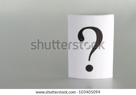big question mark on a piece of paper on a gray background