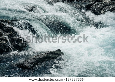 Big rapids of powerful mountain river. Beautiful background with azure water in fast river. Frozen motion of tall mountain river rapids. Power majestic nature of highlands. Backdrop of aqua turbulence ストックフォト ©