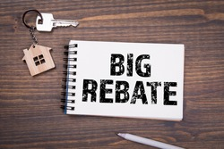 Big Rebate. Taxes, Sales, Profits and Benefits Concept. Note paper on a dark wood background