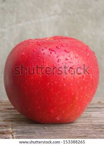 Big red apple with water drops on wooden table.