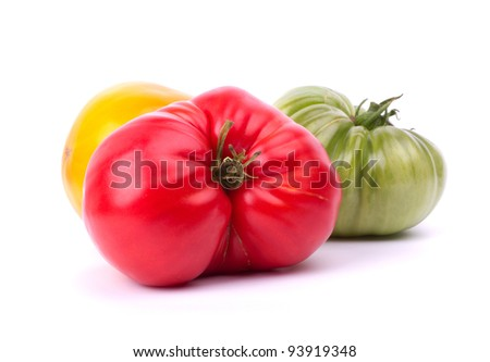 Big red, green and yellow tomatoes on white background