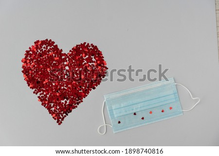 big red heart from little sparkling confeti and medical mask on light background. Copy space. Valentines day in new reality Stok fotoğraf ©