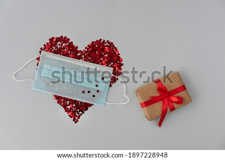 big red heart made from little glittering confeti partly covered with medical mask little gift box is near, protective measures on valentines day, new reality. Copy space Stok fotoğraf ©