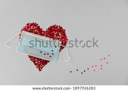 big red heart made from little glittering confeti partly covered with medical mask, trace of confeti, protective measures on valentines day, new reality. Copy space Stok fotoğraf ©