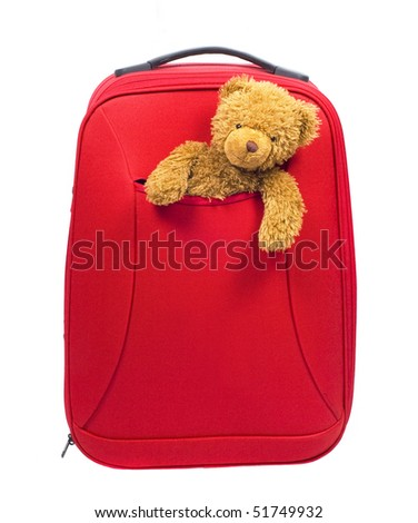 big red luggage bag and children's toy bear cub isolated