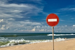 Big red road prohibiting stop sign standing on a deserted beach yellow sand blue sea shore clear blue sky summer warmth