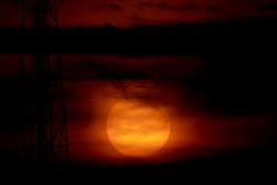 Big red sunset sky and dark cloud background, scary atmosphere on night evening time, big red sun bright over dark on center photo for graphic design, sihouette on sun down beautiful nature