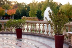 Big red vases outodoor in a park. Granite flower and stone baluster railing.
