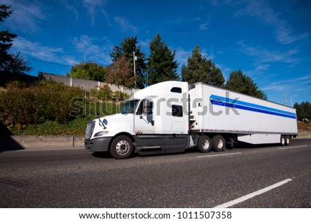 Big rig American powerful white semi truck for long haul deliveries carry refrigerator semi trailer with fresh chilled products going on the wide highway with green trees  #1011507358
