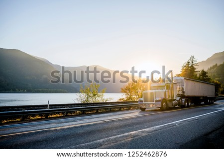 Big rig American white long haul powerful semi truck transporting commercial cargo in bulk semi trailer on straight evening road with scenic sunset in Columbia River Gorge
