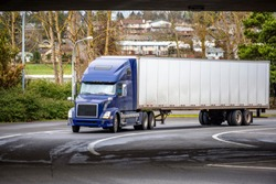 Big rig blue classic American modern semi truck with high cab for long haul routs with dry van semi trailer transporting commercial cargo driving on the turning city street going under the bridge