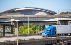 Big rig blue industrial diesel semi truck transporting cargo in refrigerator semi trailer running on the overhead road intersection across another overpass highway with heavy traffic