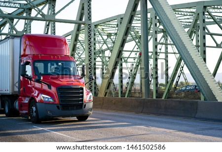 Big rig bright red day cab powerful bonnet semi truck transporting commercial cargo in dry van semi trailer with aerodynamic skirt driving on the metal truss Columbia River Interstate drawbridge