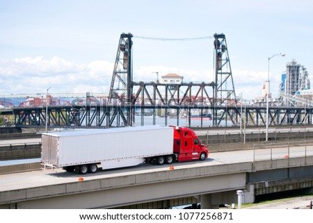 Big rig bright red semi truck transporting semi trailer with aerodynamic skirt to reduce airflow resistance on overpass road along the river with drawbridge towers and industrial area on background