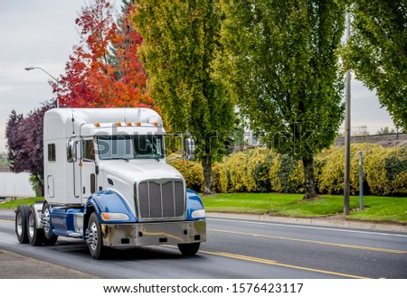 Big rig classic American bonnet semi truck tractor with high sleeping compartment for truck driver rest running on the city street road with autumn trees on the side to warehouse for loaded trailer #1576423117
