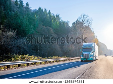 Big rig green modern bonnet American semi truck with high cab for long haul routs transporting refrigerated semi trailer driving on the straight highway in front of another traffic in sunny day