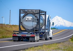 Big rig industrial grade diesel semi truck transporting danger flammable chemical cargo in a specialized reinforced tank on open bed semi trailer running on the narrow road with snow mountain view