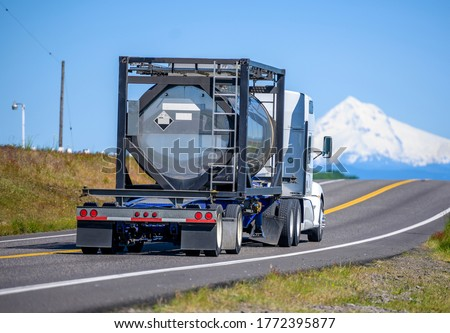 Big rig industrial grade diesel semi truck transporting danger flammable chemical cargo in a specialized reinforced tank on open bed semi trailer running on the narrow road with snow mountain view Photo stock ©