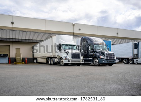 Big rig long haul industrial freight white semi truck loading commercial cargo to dry van semi trailer standing at the warehouse dock gate in row with another loaded semi trucks and semi trailers