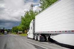 Big rig long haul industrial freight white semi truck with grille guard and refrigerator semi trailer with skirt waiting for commercial cargo parked on the street road near the warehouse buildings