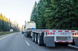 Big rig long haul powerful semi truck with empty light weight aluminum flat bed semi trailer running on the winter road in convoy with another semi trucks and evergreen trees