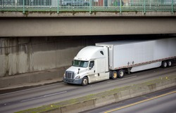 Big rig long haul white semi truck with low cab and spoiler for improve aerodynamics transporting cargo in loaded dry van semi trailer running on the wide road under the bridge across divided highway