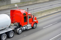 Big rig powerful diesel industrial red semi truck transporting tank semi trailer for carry liquefied gas and other gaseous chemicals cargo running on the wide highway road