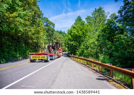 Big rig powerful heavy-duty semi truck tractor transporting oversized excavator on step down semi trailer with oversize load sign driving on the forest road with green trees #1438589441