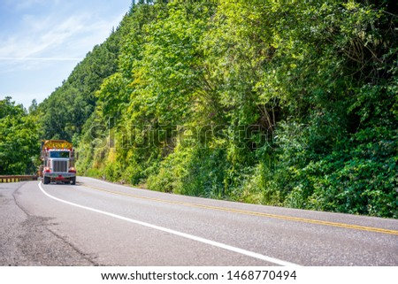 Big rig powerful heavy-duty semi truck tractor transporting oversized excavator on step down semi trailer with oversize load sign driving on the forest road with green trees #1468770494