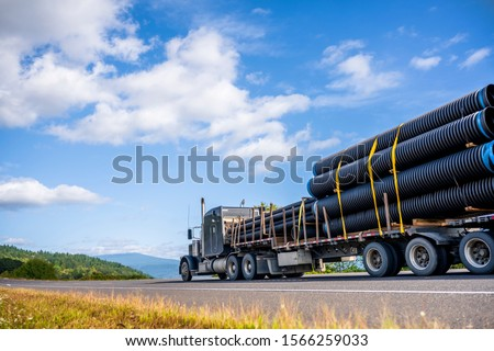 Big rig powerful professional industrial bonnet semi truck for long haul delivery commercial plastic pipes going with step down semi trailer on the summer road with green forest trees on the sides Сток-фото ©