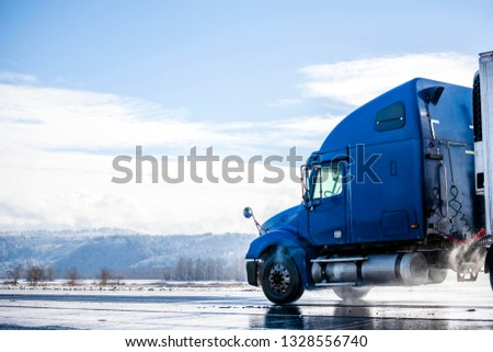 Big rig pro long haul blue semi truck tractor transporting commercial cargo in refrigerator semi trailer going on the wet glossy road with water from melting snow and winter snowy trees on the side #1328556740