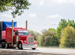 Big rig red classic American industrial semi truck tractor with sleeper cab compartment for truck driver rest transporting cargo in dry van semi trailer driving on the highway road with trees