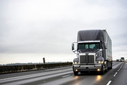 Big rig stylish industrial dark gray semi truck with turned on headlights transporting cargo in dry van semi trailer running on the twilight wet road with light reflection surface in rain weather